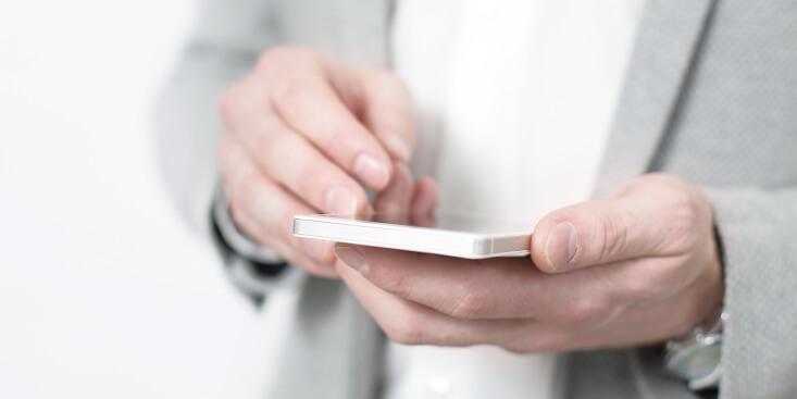 Beitragsbild Mann mit Handy in der Hand, mobile Suche neues Design Google Favicons